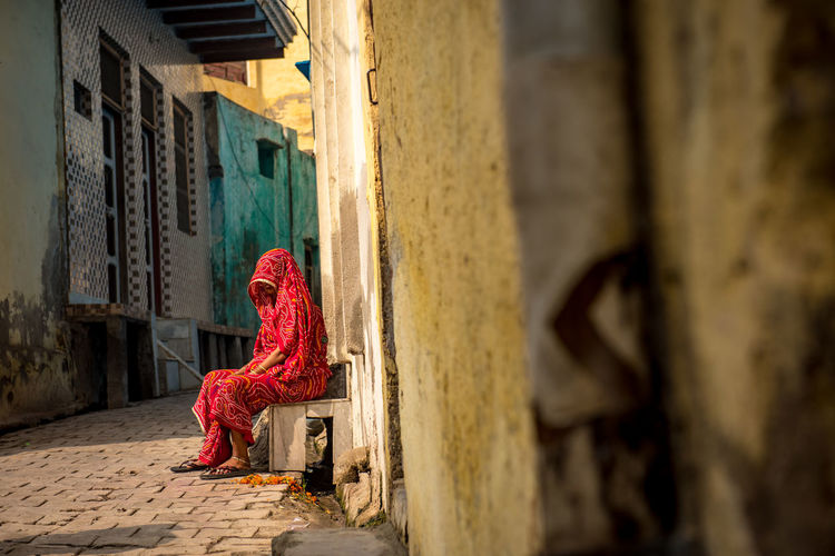 Woman In Sari Seating Outside House