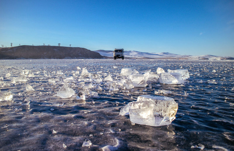 Vehicle On Frozen Lake Beikal Against Clear Blue Sky During Sunny Day