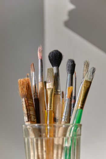 Close-up of paintbrushes on table against white background