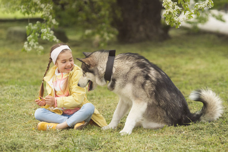 Girl with dog sitting at public park
