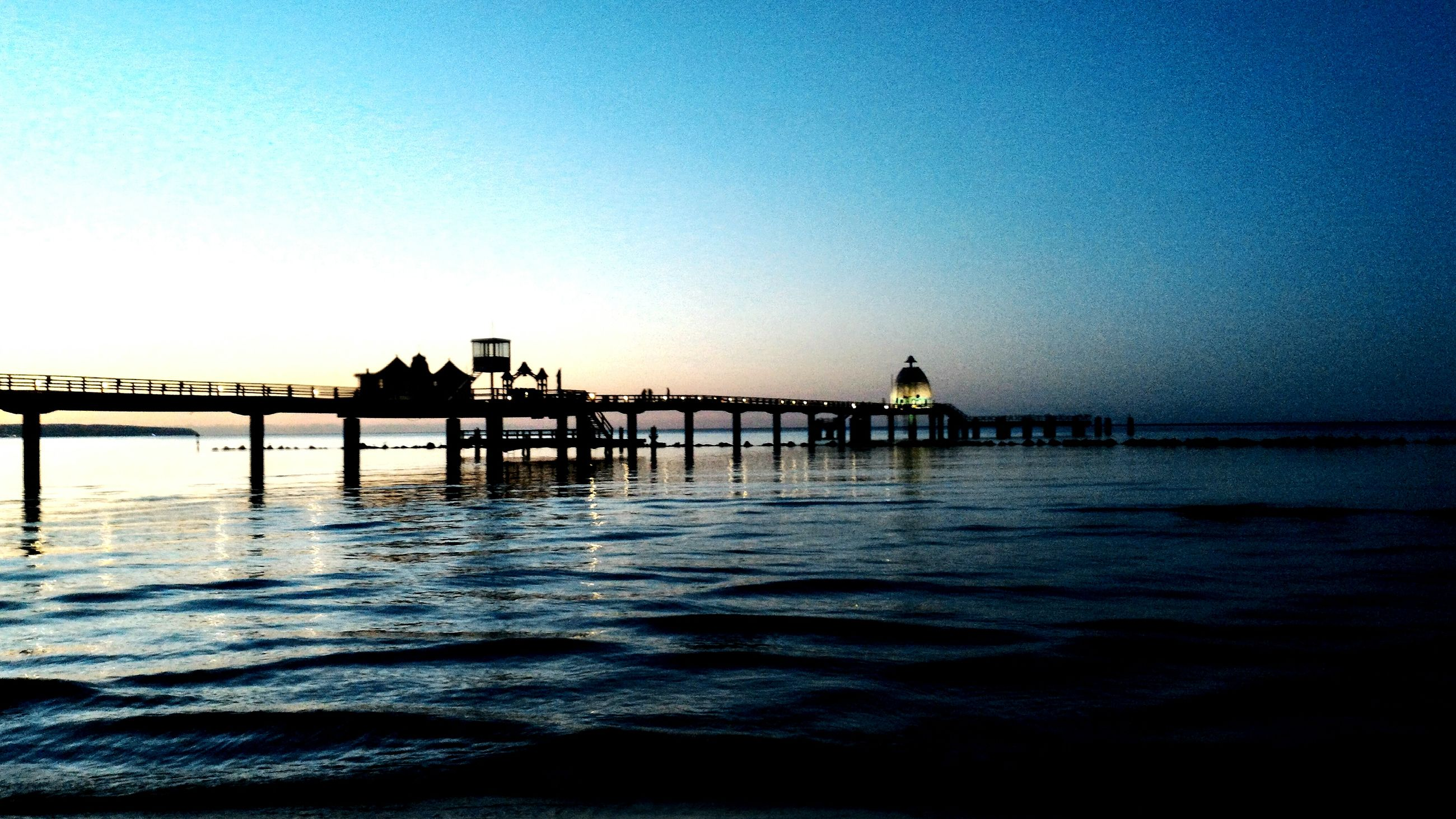 water, clear sky, copy space, pier, sea, built structure, tranquil scene, waterfront, tranquility, architecture, silhouette, sunset, scenics, blue, dusk, nature, reflection, beauty in nature, rippled, bridge - man made structure