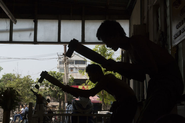 Side View Of Silhouette Men Working At Workshop