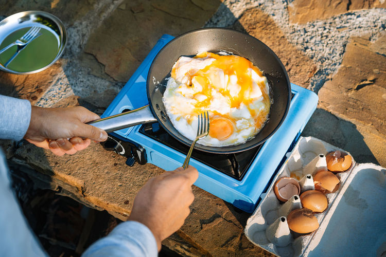 High angle view of man preparing omelet on camping stove