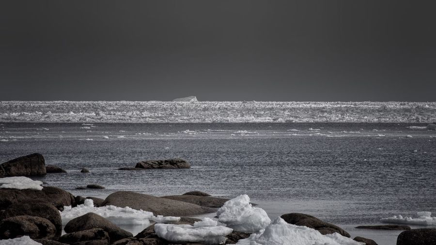 Greyed Out Wall of Ice Sea Beach Rock - Object Nature Beauty In Nature Wave Water Horizon Over Water No People Tranquility Outdoors Clear Sky Scenics Day Sky Pebble Beach