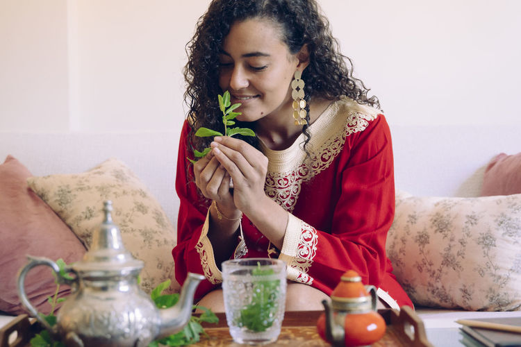 Young woman holding mint leaves while sitting by table at home