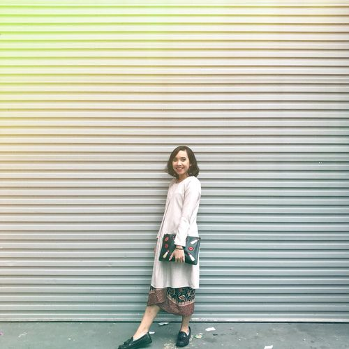 Full Length Side View Of Smiling Woman Standing Against Shutter