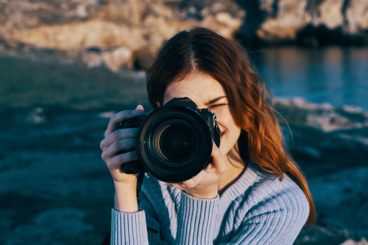 Portrait of woman photographing with camera