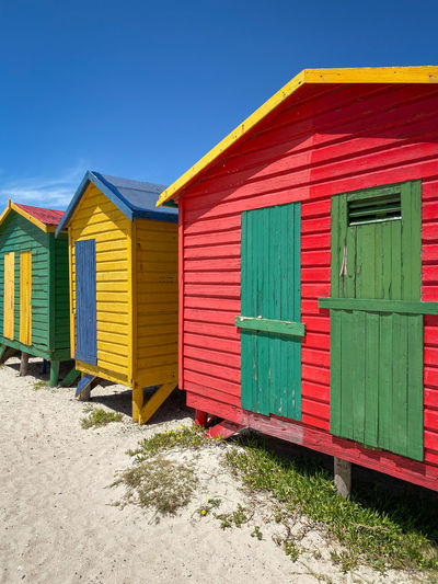 Beach huts against buildings against clear blue sky