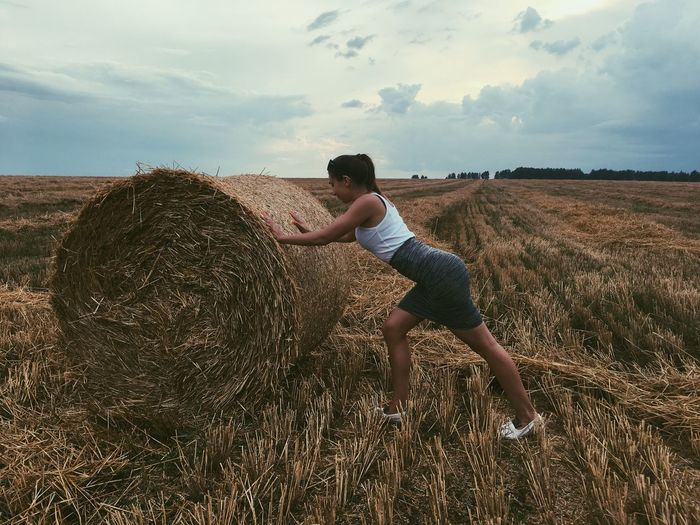 Side view of young woman pushing hay bale on grassy field against sky during sunset