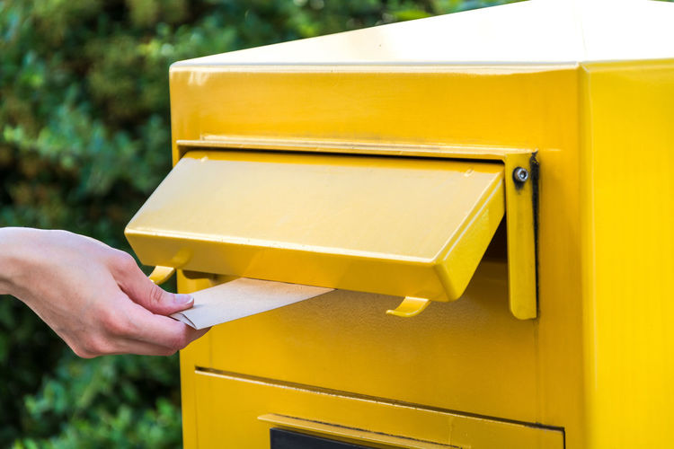 Cropped hand inserting envelope in yellow public mailbox
