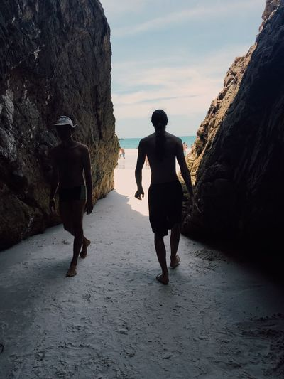 Rear view of men walking on rock