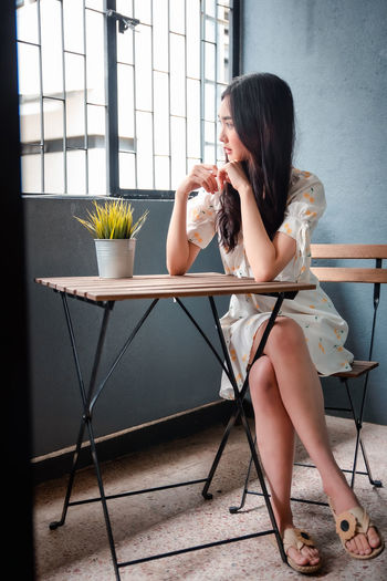 Full length of woman sitting on table