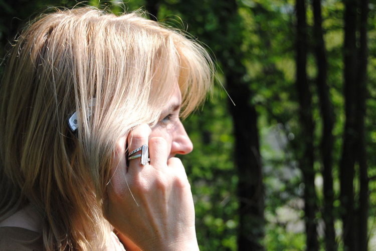 Close-up side view of woman with blond hair answering mobile phone in park