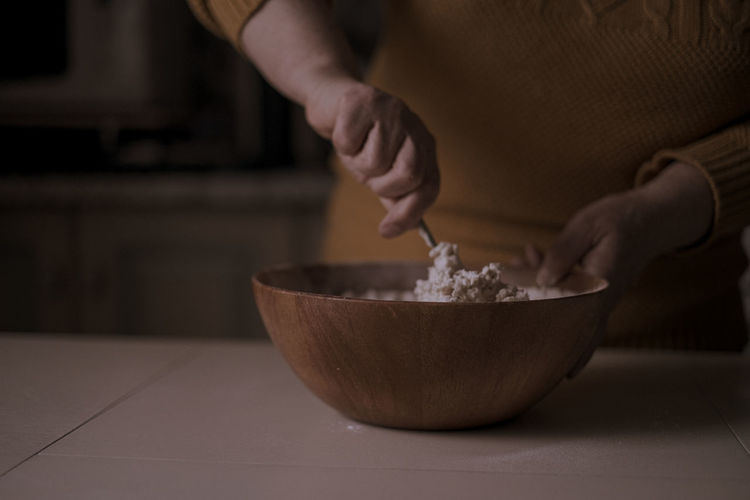 Midsection of woman preparing food in bowl on table