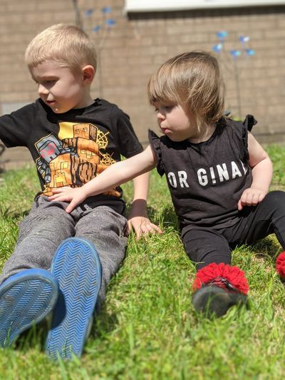 Siblings sitting on grass