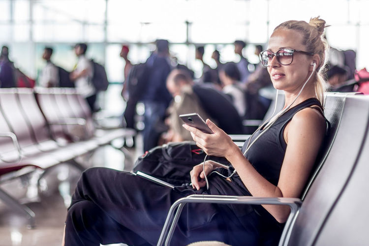 Smiling woman using smart phone sitting at airport