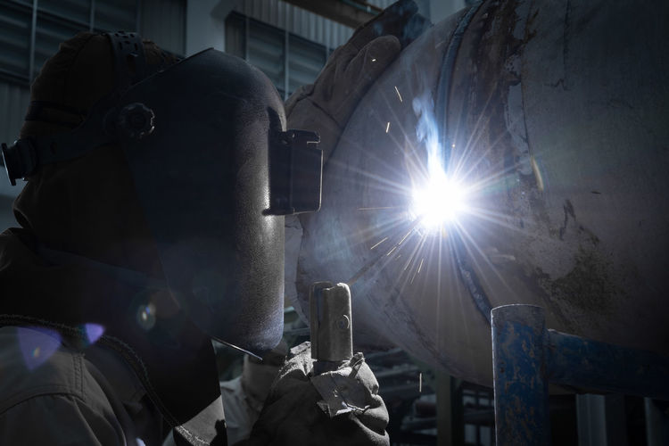 Occupation Real People Protection Protective Workwear Working Welder Holding Technology Lens Flare Welding Illuminated People Industry Security Men Safety Unrecognizable Person Indoors  Low Angle View Skill  Government