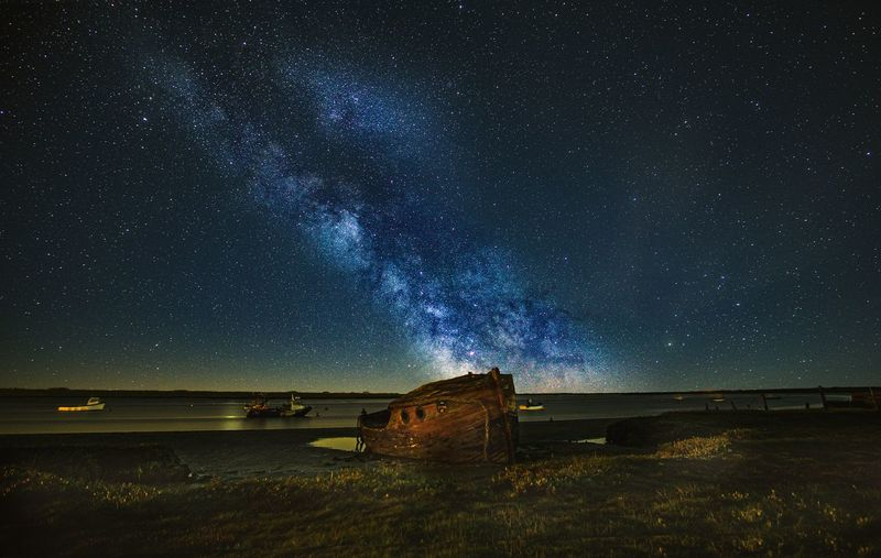 Scenic view of star field against sky at night over shipwreck