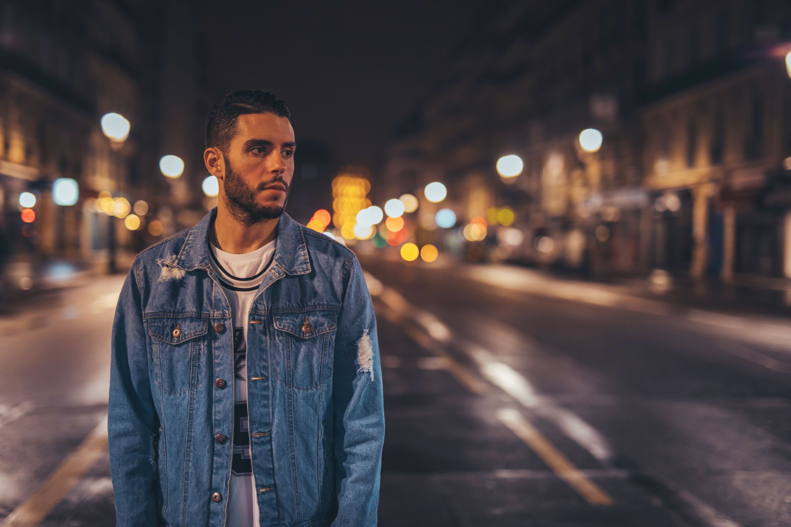 night, illuminated, street, front view, focus on foreground, jacket, one person, young adult, outdoors, city, casual clothing, building exterior, lifestyles, real people, portrait, fashion, winter, looking at camera, built structure, warm clothing, denim jacket, cold temperature, architecture, young women, people