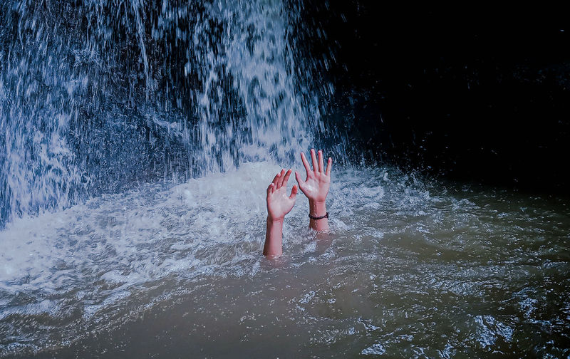Low section of woman splashing water in sea