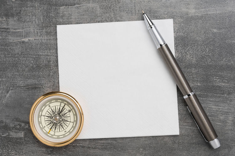 Compass with clean napkin and a metal ballpoint pen on grey background Paper Table Cement Compass Decisions Napkin Pen Copy Space Gray Write Background Travel Strategy Direction Objective Business Goal Ideas Inspiration Motivation Note Taking Notes Planning Concept Doodle