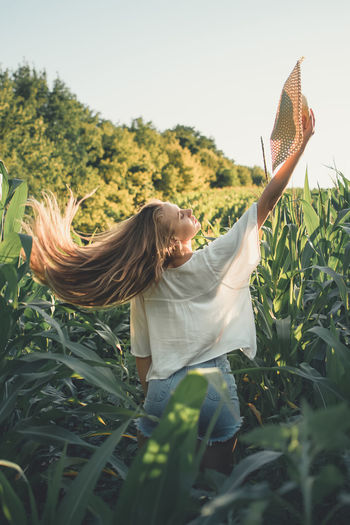 Woman with straw hat on corn  field against sky