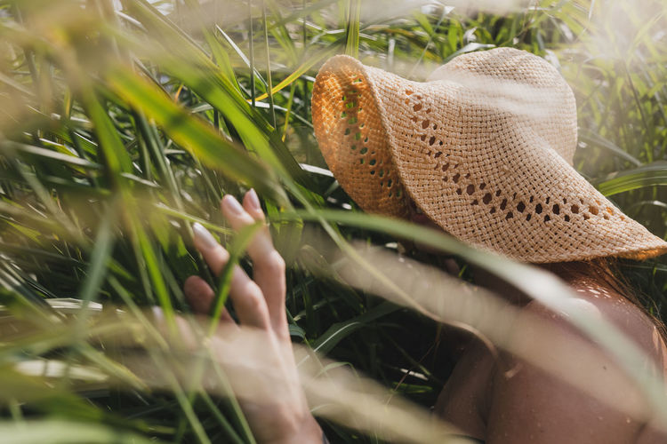 Woman wearing hat seen through plants
