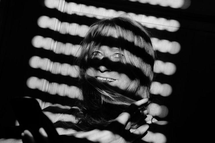 Portrait of smiling mature woman in darkroom