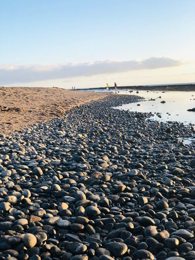 Surface level of stones on beach against sky