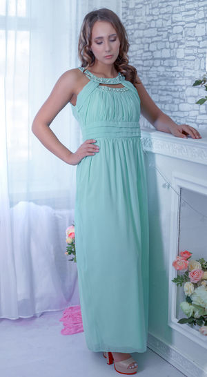 Beautiful Woman Standing In Turquoise Dress At Home