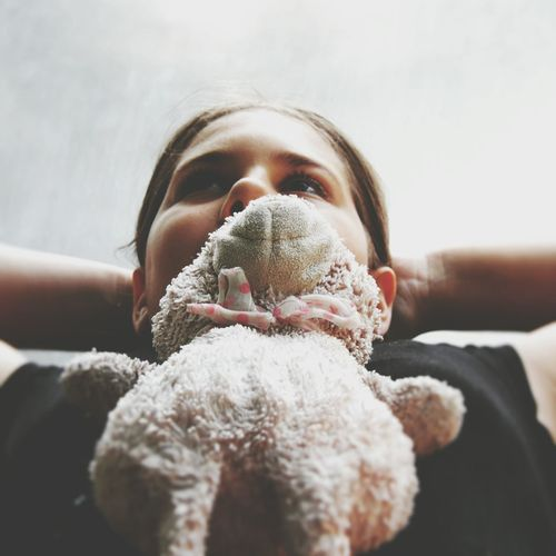 Close-Up Of Girl With Toy Against Wall