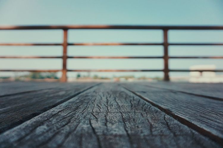 Close-up of boardwalk against clear sky