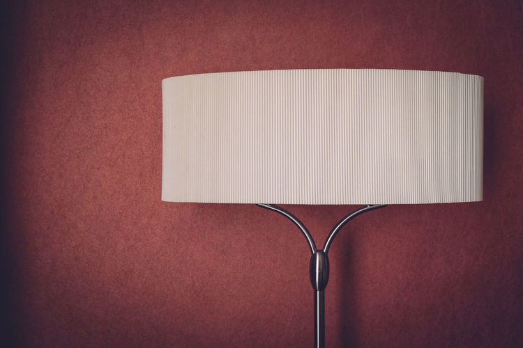 Close-up of lampshade against maroon wall