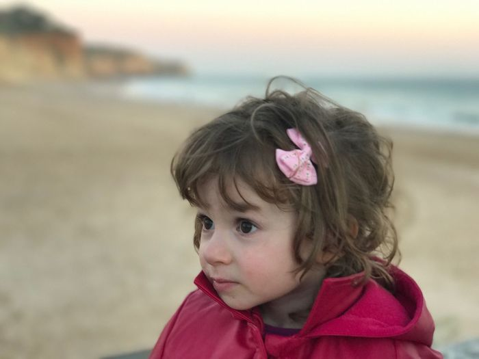 Close-up of cute girl wearing hair bow at beach during sunset