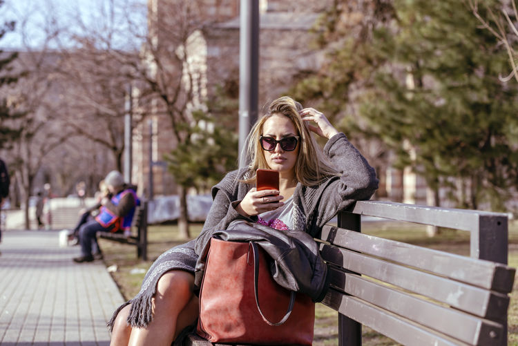 Woman using mobile phone while sitting on bench