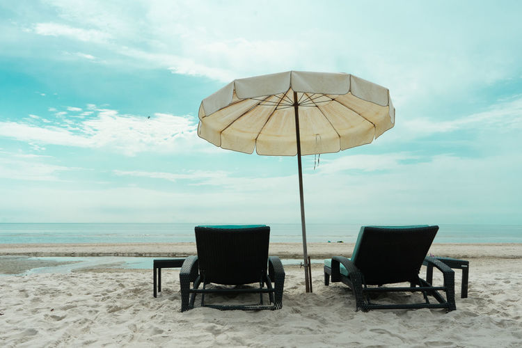 Closeup pair of beach bench on the beach with flying bird in the sky and horizontal skyline above the sea in background Chair Land Beach Sky Seat Cloud - Sky Sea Water Horizon Over Water Horizon Beauty In Nature Sand Nature Scenics - Nature Tranquil Scene Absence No People Day Tranquility Outdoors Umbrella Summer Travel Destinations Relaxation Chill Rest Blue Sky