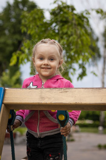 Portrait of a smiling girl holding wood