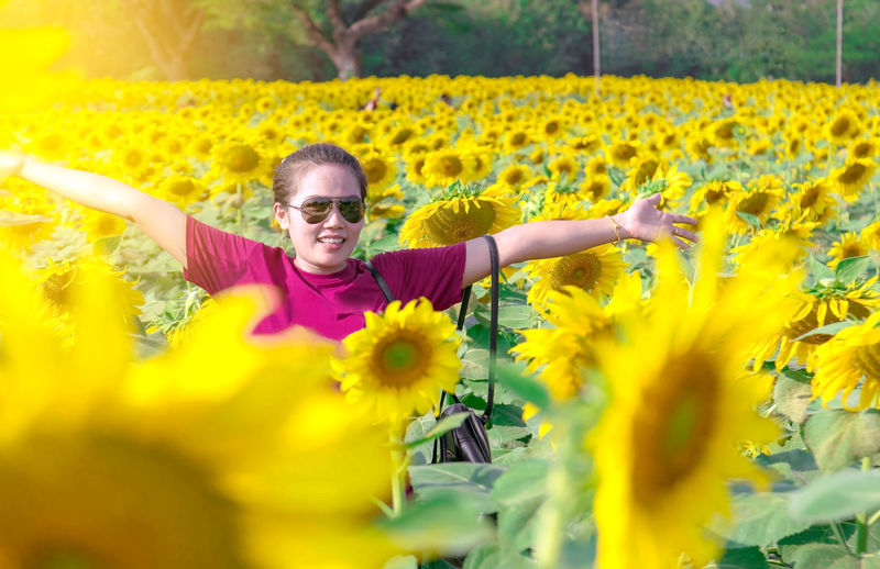 Asian woman wearing sunglasses standing poses in the middle of sunflower fields.