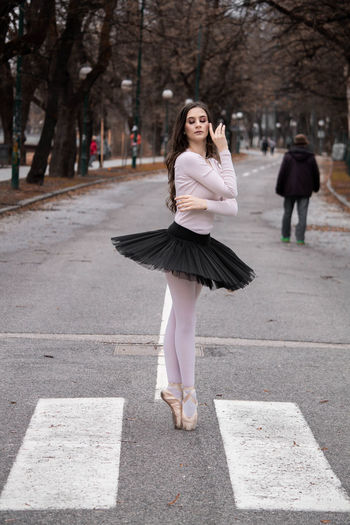 Side view of ballerina dancing on road