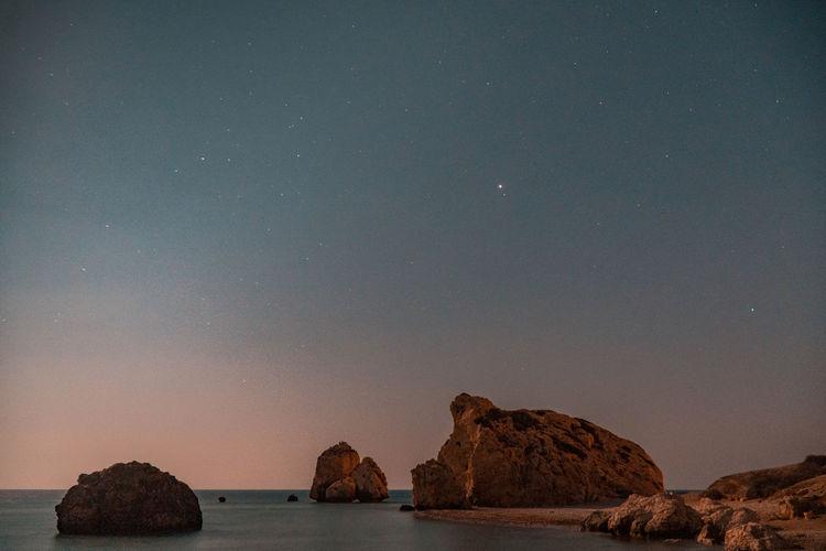 Rocks in sea against sky at night