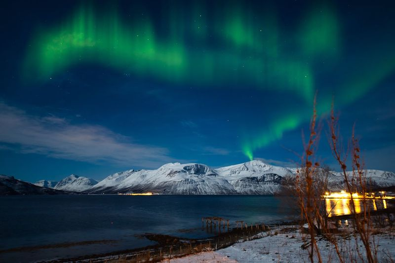 Northern lights covered on the snowy mountains in the arctic area of norway