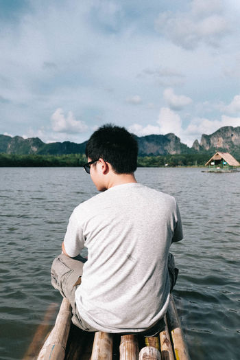 Rear view of man sitting on wooden raft over lake against sky