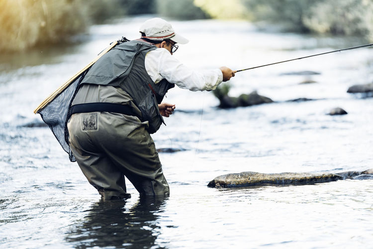Side view of a man fishing in river