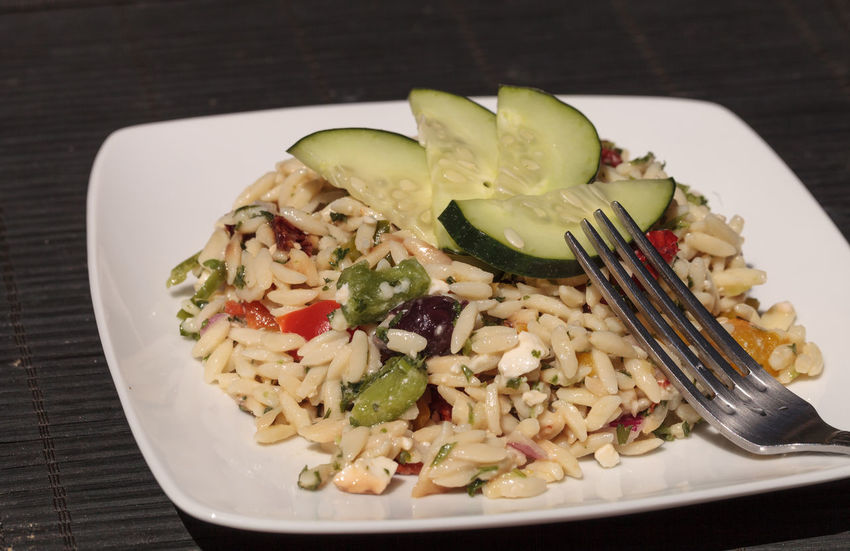 Greek orzo salad with cucumbers, sundried tomatoes, olives, onions, peppers and feta cheese on a white plate with a silver fork. Cucumber Feta Cheese Food Food And Drink Freshness Greek Healthy Eating No People Olives Orzo Peppers Ready-to-eat Red Pepper Salad Sundried Tomato Tomato