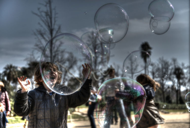 Reflection of people in bubbles against sky