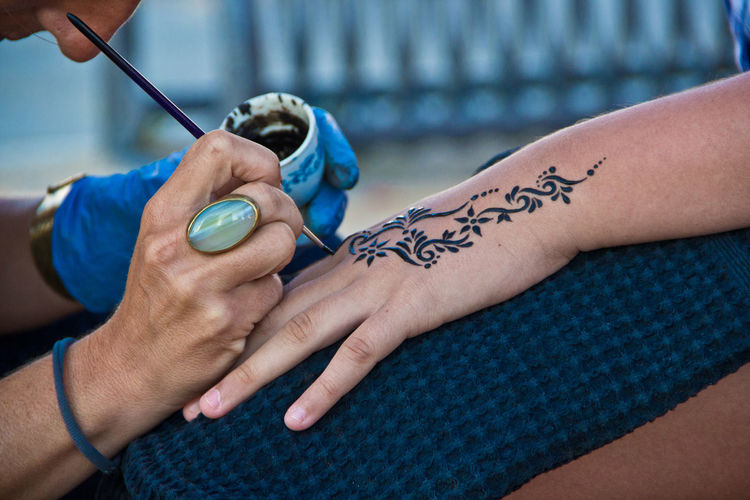 Cropped Image Of Artist Making Henna Tattoo On Female Hand