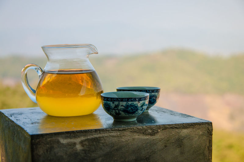 Tea in jug with cups on table against mountain