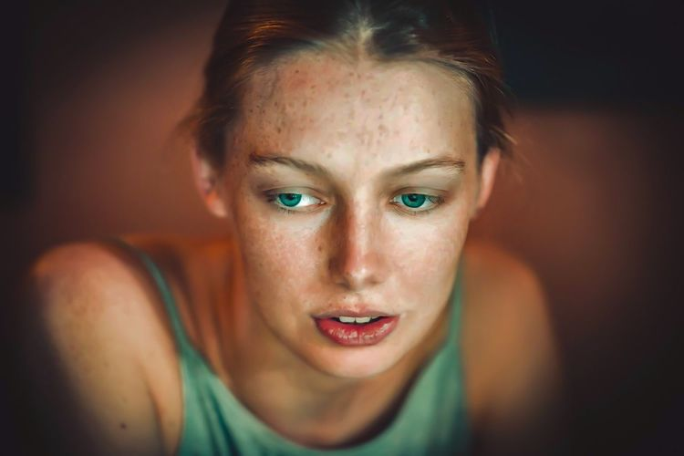 Close-up of thoughtful young woman with green eyes