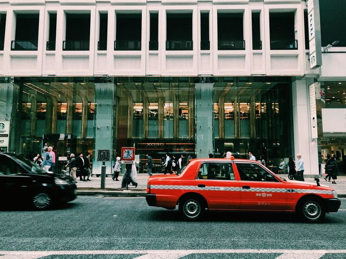 red taxi Transportation Motor Vehicle City Architecture Car EyeEmNewHere Building Exterior Built Structure Land Vehicle Street Road City Life Day Outdoors Red City Street Illuminated Building Traffic Incidental People