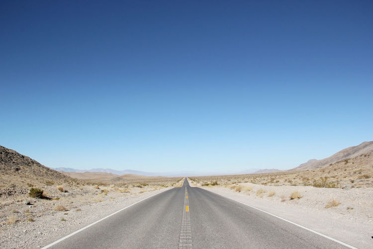 Empty road in desert against clear blue sky